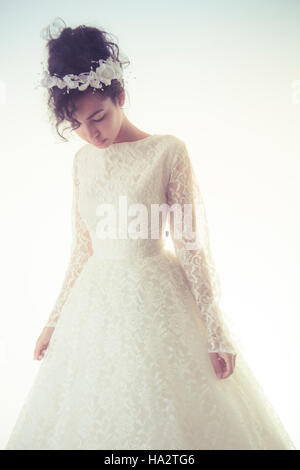 Bridal wedding photography: A young olive skinned woman wearing a white wedding dress standing in front of a white - Stock Photo