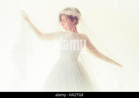 Bridal wedding photography: A young olive skinned woman wearing a white wedding dress and a veil  standing in front - Stock Photo