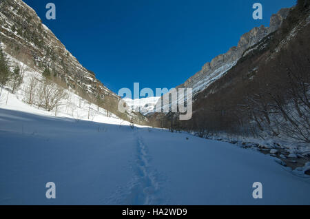 Footprints in the snow in a high valley, Ordesa y Monte Perdido National park - Stock Photo