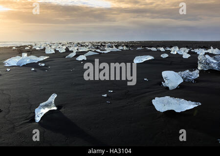 Icebergs on a black sand volcanic beach next to the Jokulsarlon iceberg lagoon in Vatnajokull national park, Iceland - Stock Photo