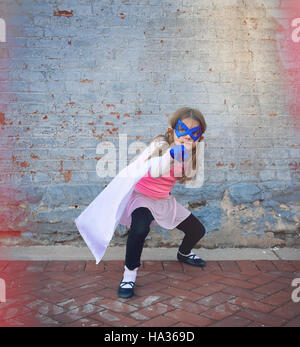 A little super hero child is standing outside against an old vintage brick wall for an education or creative concept. - Stock Photo
