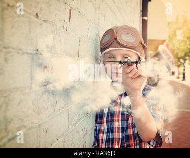 A young boy is pretending to be a pilot and playing with an airplane toy against a brick wall for a dream or career - Stock Photo