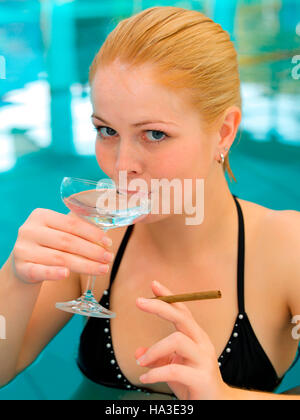 Young woman with sparkling wine and a cigar in the pool - Stock Photo