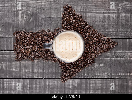 Large cup with hot cappuccino with coffee beans on wooden board - Stock Photo
