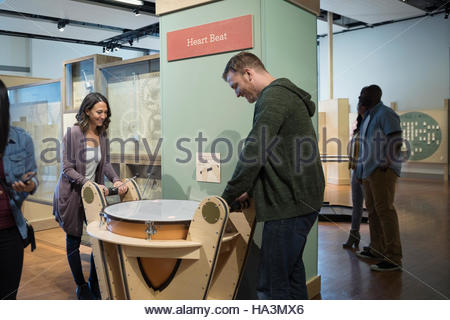 Couple at heart beat drum exhibit in science center - Stock Photo