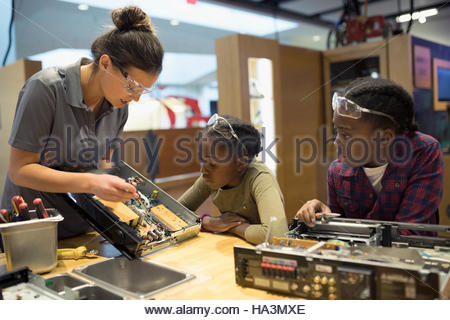 Scientist teaching twin sisters assembling electronics in science center - Stock Photo