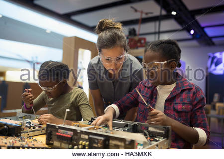 Scientist watching twin sisters assembling electronics in science center - Stock Photo