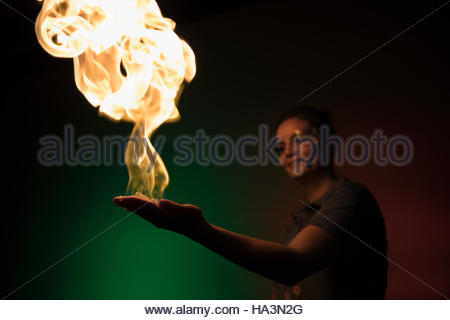 Scientist creating fire demonstration in palm of hand in science center - Stock Photo