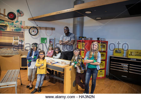 Portrait smiling scientist and children at workshop display in science center - Stock Photo
