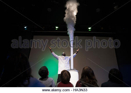 Children watching scientist demonstrating geyser cloud in science center theater - Stock Photo
