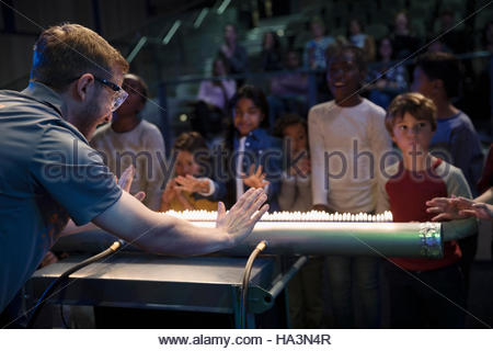 Children and scientist creating acoustic waves using a Rubens tube in science center theater - Stock Photo