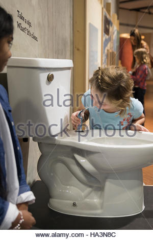 Girls drinking from toilet water fountain in science center - Stock Photo