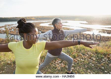 Women practicing yoga warrior 2 pose on autumn hilltop overlooking lake - Stock Photo
