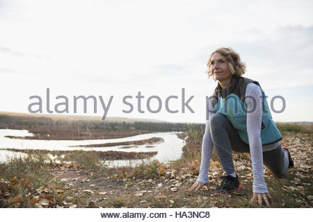 Woman practicing yoga low lunge on autumn hilltop overlooking lake - Stock Photo