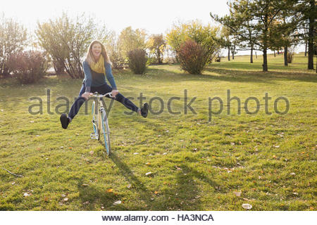 Playful woman riding bicycle in sunny autumn park - Stock Photo