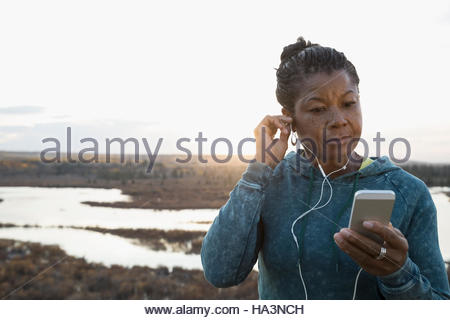 Woman runner listening to music with mp3 player and earbuds overlooking lake - Stock Photo