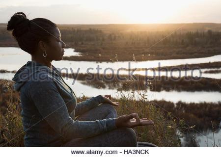 Serene woman meditating in lotus position on autumn hillside overlooking lake at sunset - Stock Photo