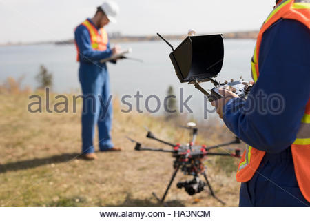 Surveyors with drone equipment at sunny lakeside - Stock Photo