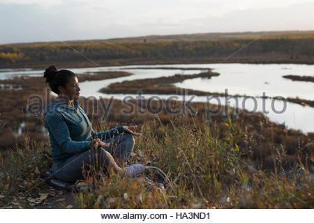 Serene woman meditating in lotus position on autumn hillside overlooking lake - Stock Photo