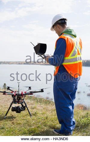Surveyor with drone equipment at sunny lakeside - Stock Photo