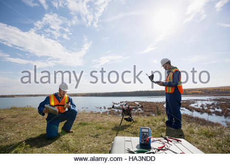 Surveyors with drone equipment on sunny hilltop overlooking lake - Stock Photo