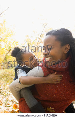 Mother piggybacking daughter in autumn park - Stock Photo