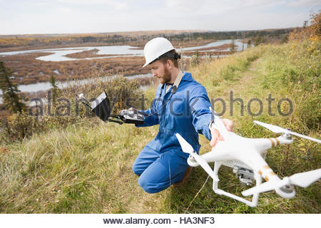 Surveyor with drone equipment on hillside - Stock Photo