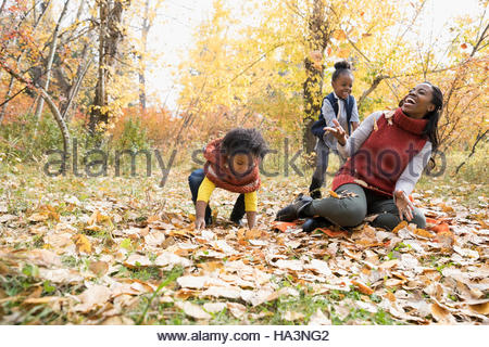 Mother and daughters playing throwing autumn leaves in park - Stock Photo