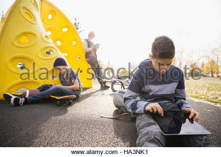 Tween boys using digital tablets and cell phone in sunny autumn park - Stock Photo