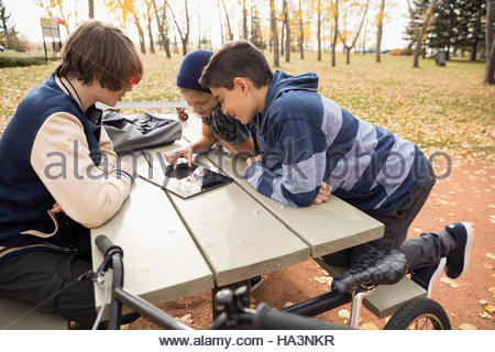 Tween boys using digital tablet on picnic table in autumn park - Stock Photo