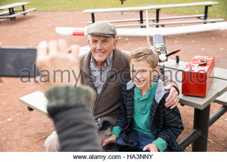 Woman with camera phone photographing father and son with model airplane in park - Stock Photo