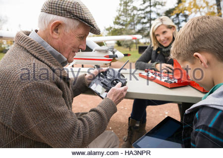 Senior man and grandson with model airplane remote control and digital tablet in park - Stock Photo