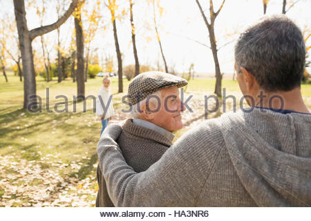 Father and son walking and hugging in sunny autumn park - Stock Photo