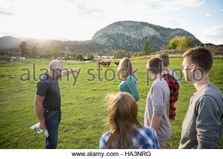 Family watching father pointing to cows in field on rural farm - Stock Photo