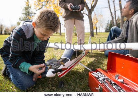 Boy fixing model airplane with father and grandfather in park - Stock Photo