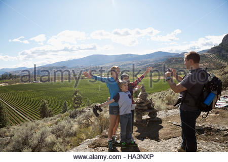 Father with camera phone photographing family hiking above sunny rural vineyard - Stock Photo
