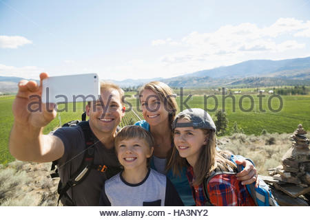 Family with camera phone taking selfie hiking near sunny rural vineyard - Stock Photo