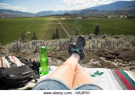 Personal perspective woman hiker relaxing looking at sunny rural view - Stock Photo