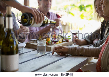 Couples wine tasting and enjoying charcuterie board on patio at winery tasting room - Stock Photo