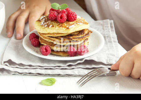 Child eating healthy breakfast at home - pancakes with raspberries on plate with children hands - Stock Photo