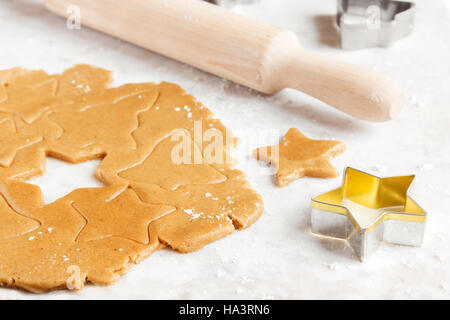 Preparing Christmas gingerbread cookies with cutter, ginger dough - homemade festive Christmas bakery - Stock Photo