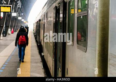 A passenger walks along the platform at Milan Railway Station, about to board a Trenitalia train. - Stock Photo