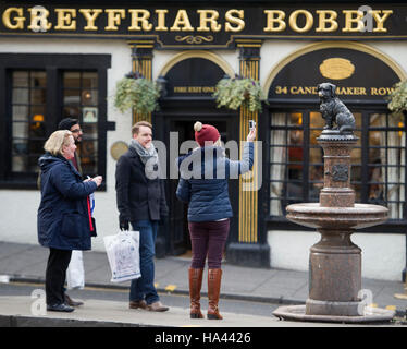 Tourists photograph Greyfriars Bobby statue which sits outside Greyfrairs Kirk on, George iv Street Bridge  in Edinburgh. - Stock Photo