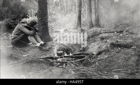 young woman sitting in the forest alone by the fire - Stock Photo