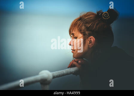 young woman resting her head on a pole looking at the sea - Stock Photo