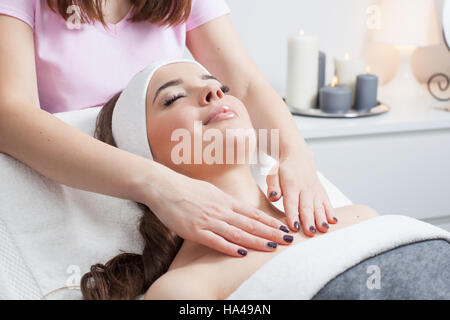Beautiful young woman receiving facial massage with closed eyes in a spa salon - Stock Photo