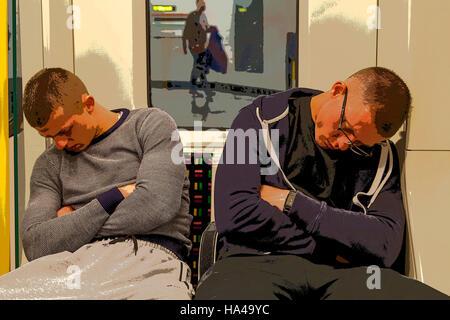Two Men Sleeping On A London Underground Train, London, UK - Stock Photo