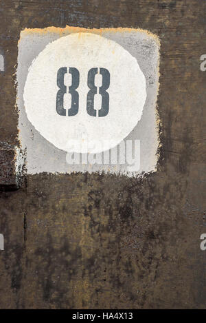Aged and worn vintage number 88 in a white circle, inside a grey square, and on a back grunge style background - Stock Photo