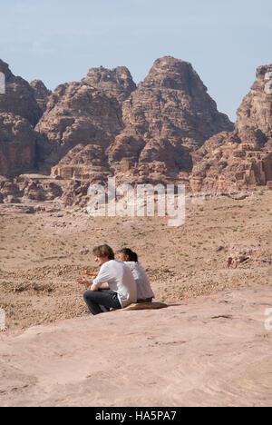 Tourists enjoy the spectacular views of Petra rocks and mountains In Jordan - Stock Photo