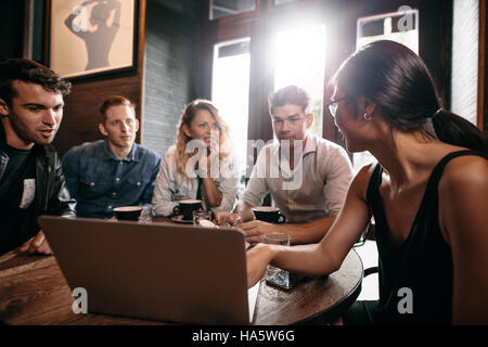 Smiling friends spending their time in coffee shop and discussing something while looking at laptop. Woman showing - Stock Photo